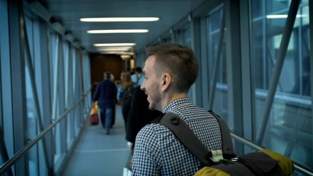 il giovane uomo va lungo il corridoio per salire a bordo dell'aeromobile - pantaloncini video stock e b–roll