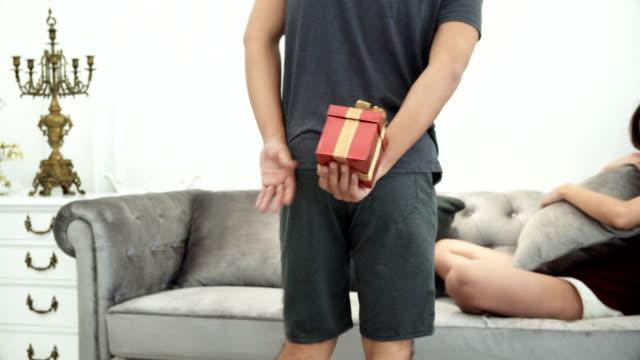 the young man hiding gift box behind to apologize girlfriend - chiedere scusa video stock e b–roll