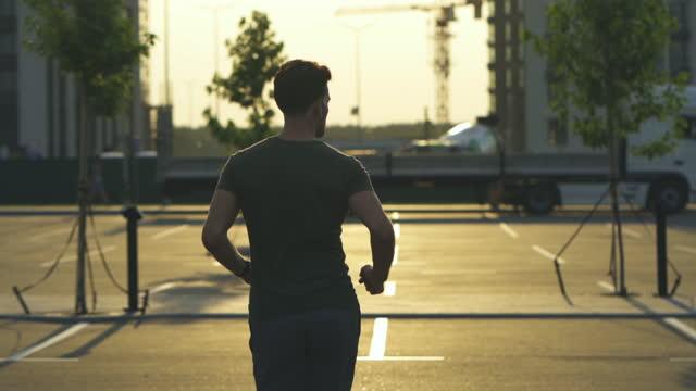 il giovane sta facendo jogging al mattino. rallentatore - auricolari wireless video stock e b–roll