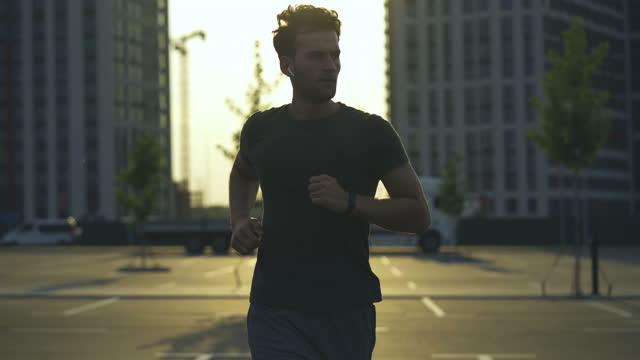 il giovane fa jogging al mattino - auricolari wireless video stock e b–roll