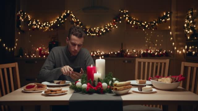 der junge mann wartet zu hause auf freunde für eine weihnachtsfeier. keiner seiner freunde kam zur weihnachtsfeier. er bläst die kerzen traurig und allein aus. - einsamkeit stock-videos und b-roll-filmmaterial