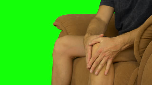 The young man sits on a brown beige chair and rubs his knee with his hands. video