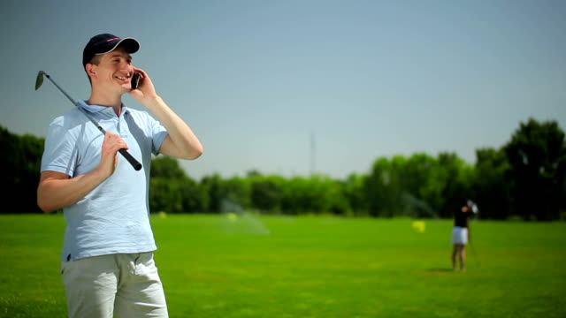 The young man talking on the phone at the course video