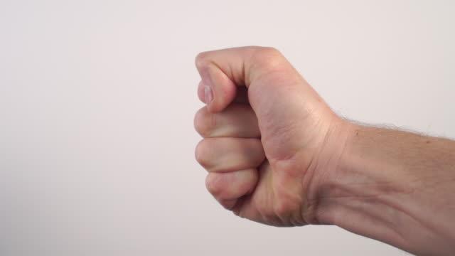 若い男はしっかりと拳に彼の指と手のひらを握ります - 対立点の映像素材/bロール