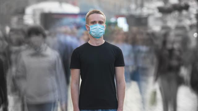 tıbbi yüz maskesi olan genç adam kalabalık akıntıda duruyor. zaman atlamalı - maske stok videoları ve detay görüntü çekimi