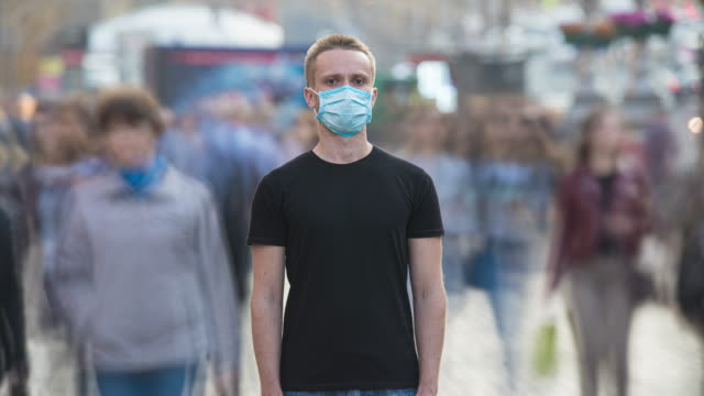 The young man with medical face mask stands in the crowdy flow. time lapse - vídeo