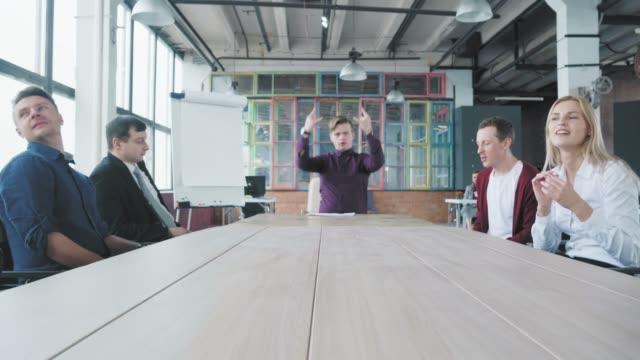 Der junge Manager sitzt gut gelaunt an einem großen Tisch und wartet auf den Beginn des Treffens, tanzt sitzend und hat Spaß. Kollegen sitzen in der Nähe. Trendigebüro-Interieur. Co-Working – Video