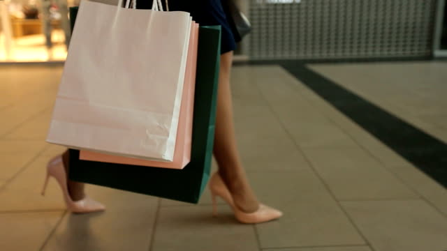 the young pretty woman walks with shopping bags in the trade center - borsa della spesa video stock e b–roll