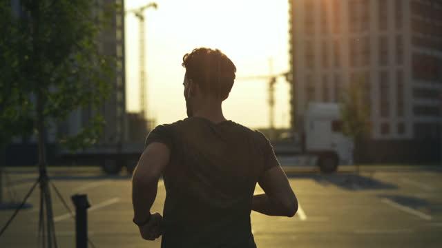 il giovane sportivo che corre al mattino - auricolari wireless video stock e b–roll