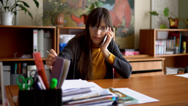 the young teacher in glasses in the classroom use a telephone. - insegnante video stock e b–roll