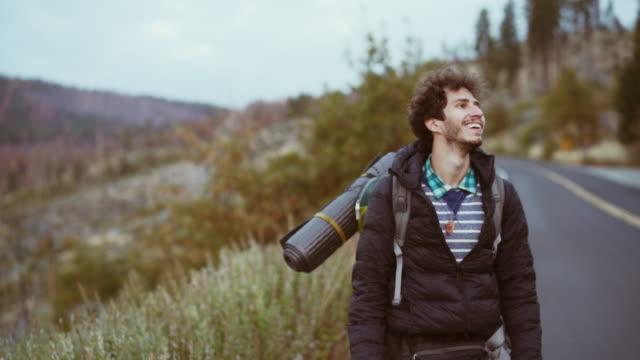 stockvideo's en b-roll-footage met de jonge reiziger man lopen met de grote rugzak op de weg van de oude platte oak in het yosemite nationaal park - niet gecultiveerd