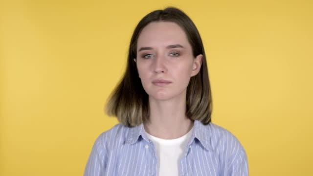 the young woman shaking head to deny on yellow background - negacja filmów i materiałów b-roll