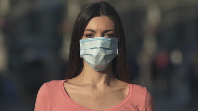 den unga kvinnan med medicinsk ansiktsmask står i mängden - face mask bildbanksvideor och videomaterial från bakom kulisserna