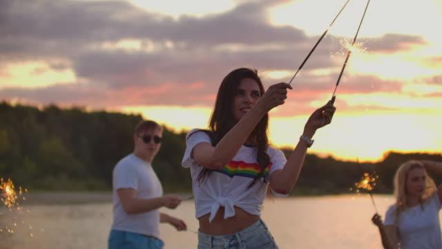 stockvideo's en b-roll-footage met theamy open air party met bengaalse lichten op het strand bij zonsondergang - t shirt