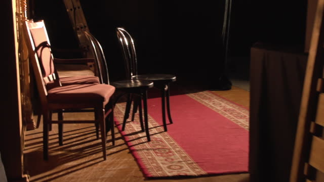 Theater backstage walk chairs decorations ladder in spotlight behind curtain Theater backstage walk chairs decorations ladder in spotlight curtain behind the scenes theatrical prop stock videos & royalty-free footage