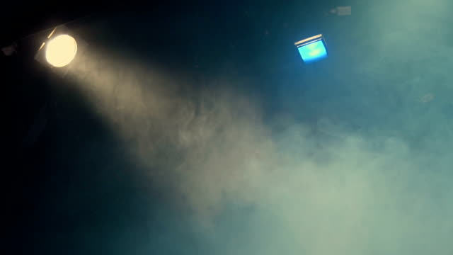Theatrical smoke. The rays of light from the floodlights at the theater during the performance. Gradual turning off of the light source with dimmer switch. Lighting equipment video