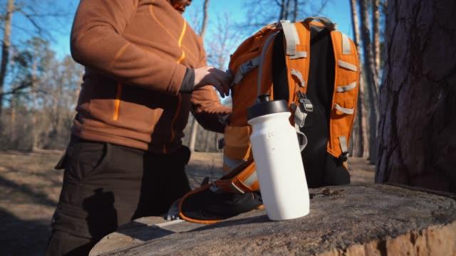 テーマハイキングと旅行。白人の観光男性は、オレンジ色のバックパックを解凍し、彼のものを取り出し、森の中の切り株にそれらを置きます。キャンプのための機器やもの。 - 荷造り点の映像素材/bロール