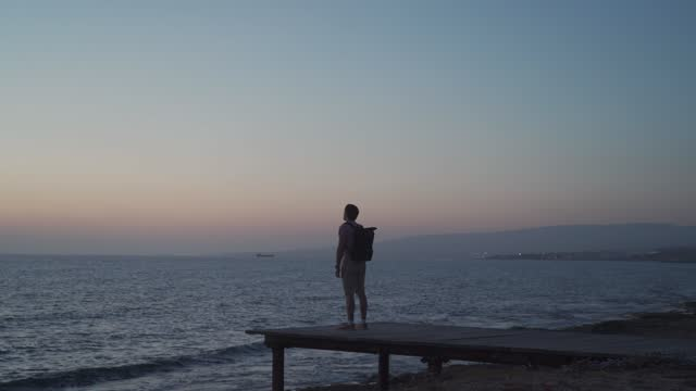 Theme of loneliness, depression, search for answers to questions while traveling. Man traveler with backpack looks at sunset of Mediterranean sea from wooden pier on island of Cyprus, city of Paphos