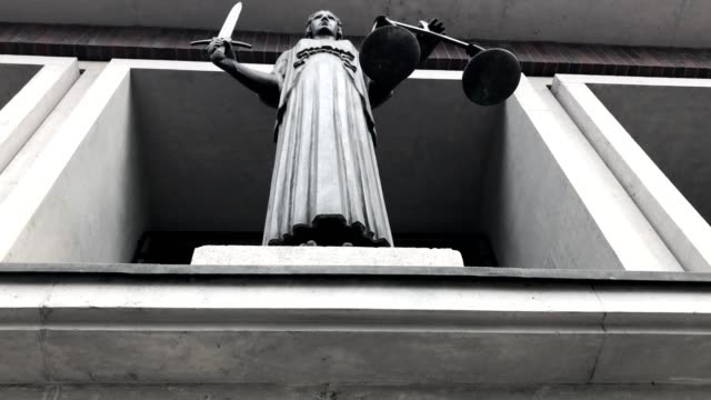 Themis with scale and sword in court video