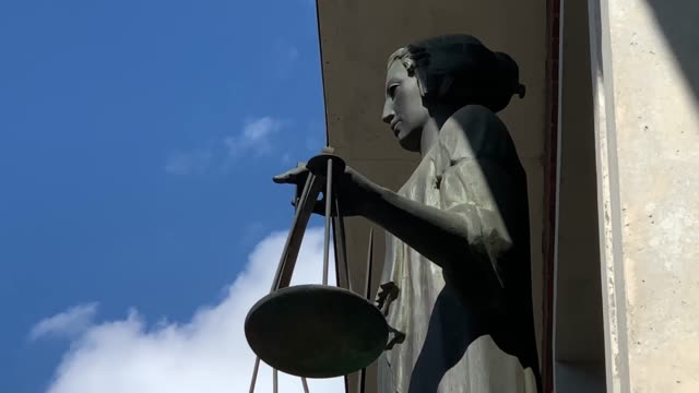 Themis with scale and sword in front of court