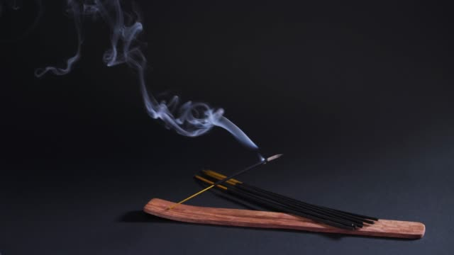 Therapeutic oriental smoke. Aromatherapy, relaxation and yoga. Smoke from aroma sticks moves on a black background 4k