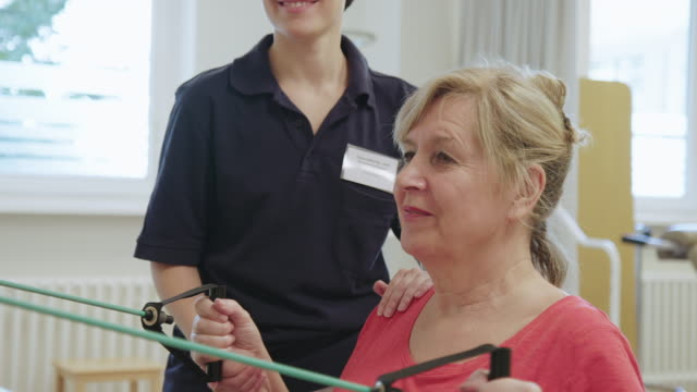 therapist assisting woman with resistance band - fisioterapia video stock e b–roll