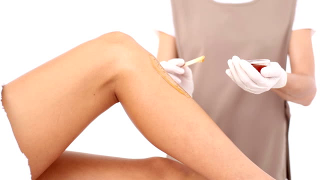 Therapist waxing womans leg at spa center video