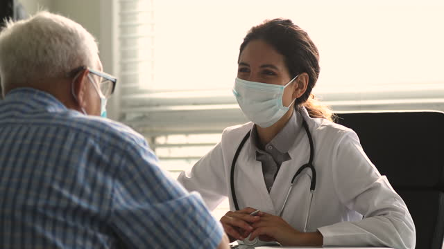 Therapist wear facemask talk to elderly patient during visit Therapist wear white coat face mask due corona virus pandemic outbreak talk to elderly patient during visit in clinic office, supporting him, telling about health check up, disease treatment concept cardiologist stock videos & royalty-free footage