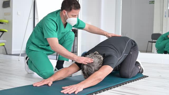terapista con maschera facciale protettiva assistere il paziente con esercizi di stretching. riprese 4k di alta qualità. - china drug video stock e b–roll
