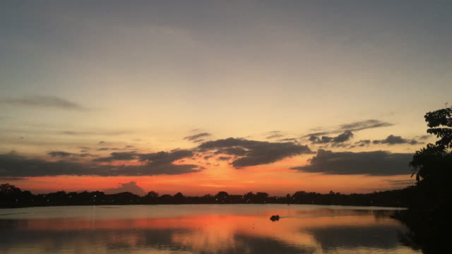 There are people boating in the river at sunset and the beautiful sky.