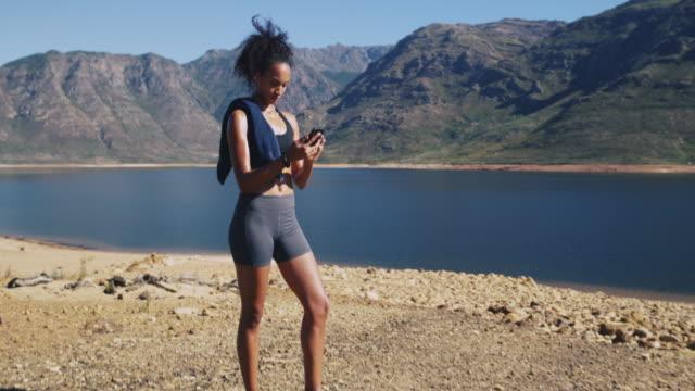det finns gott om appar för att hjälpa din träning rutin - black woman towel workout bildbanksvideor och videomaterial från bakom kulisserna