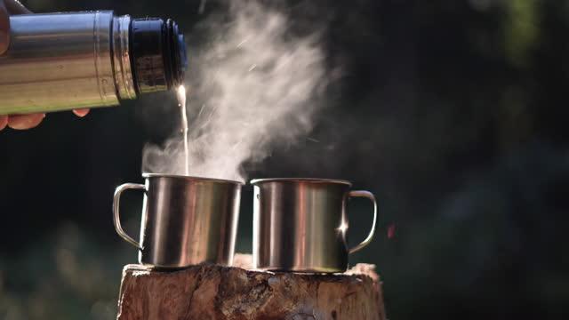 vidéos et rushes de il ya deux tasses sur un chanvre en bois, un thermos verse du café chaud dans l'un d'eux - boisson chaude