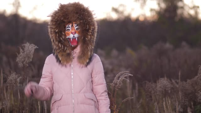 there is a girl in the park behind her. she is dressed in a pink down jacket, on the head of the hood. the girl turns around, instead of the face of the tiger's mask 4k slow mo - głowa zwierzęcia filmów i materiałów b-roll