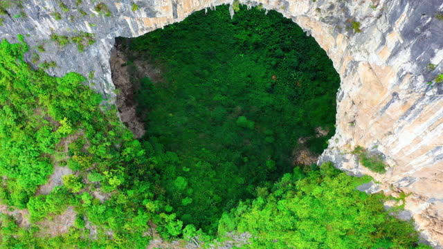 There is a huge cave in the virgin forest This is the karst landform of Leye, Guangxi, China rock formations stock videos & royalty-free footage