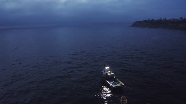 There's no better place to be 4k aerial drone footage of two men on a boat at sea in the evening recreational boat stock videos & royalty-free footage