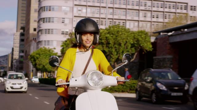 There's no better way to commute 4k video footage of a woman riding her scooter through the city crash helmet stock videos & royalty-free footage