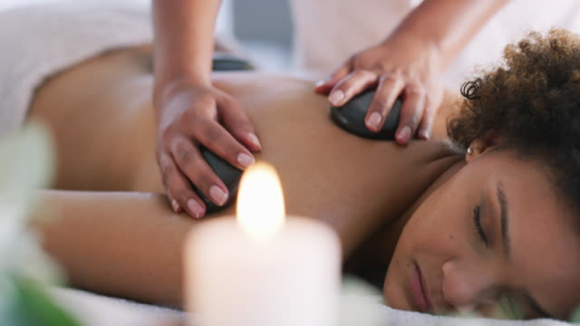There's nothing like hot stone massage to relieve body pain 4k video footage of a young woman getting a hot stone massage at a spa spa treatment stock videos & royalty-free footage