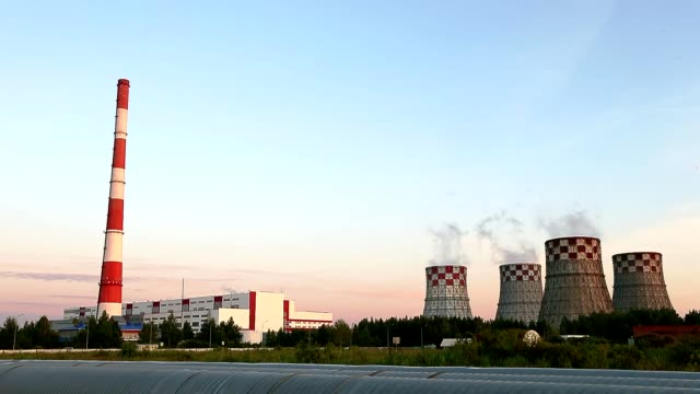Thermal Power Station edge of city summer evening dolly shot. Smoke go up to blue sky. Energy production and pollution. This is a modern urban landscape. Chimney-stalk and ecology problem on Earth. video