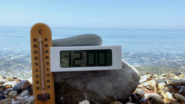 vídeos de stock e filmes b-roll de thermometer show the temperature of air at midday at the beach - climate clock