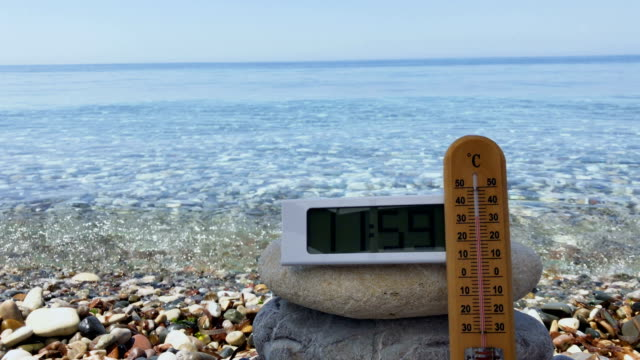 vídeos de stock e filmes b-roll de thermometer show the temperature of air at the midday near the sea - climate clock