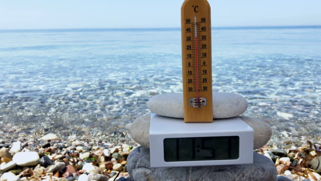 vídeos de stock e filmes b-roll de thermometer with electronic clock at sea background - climate clock