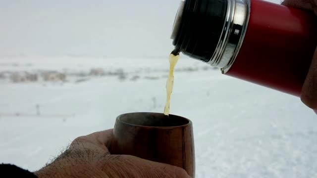 Thermos tea and small tea mug on ski track video