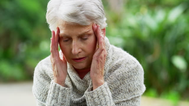These headaches are a cause for concern 4k video footage of a senior woman suffering from a headache in the park pain stock videos & royalty-free footage