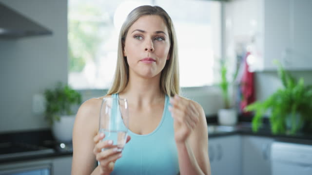These multivitamins help bolster my day 4k video footage of an attractive and healthy young woman taking her medication with a glass of water at home nutritional supplement stock videos & royalty-free footage