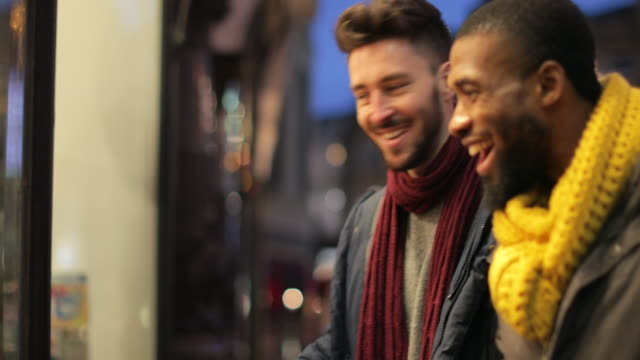They Found the Perfect Present Tracking shot of two young men walking over to a shop window and looking in shop windows as they do their christmas shopping. multi ethnic group stock videos & royalty-free footage
