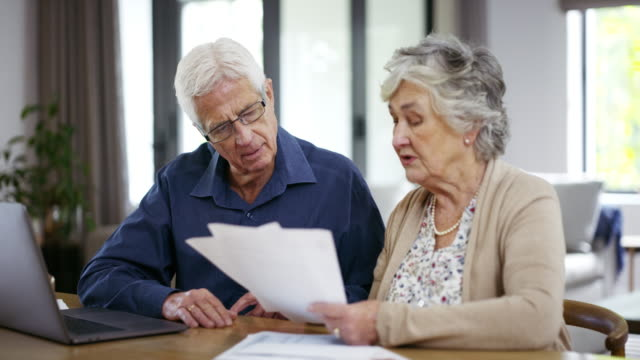 They handle their own financial affairs 4k footage of a senior couple going over some paperwork while using a laptop financial bill stock videos & royalty-free footage