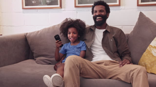They love this program! 4k video footage of a father and son sitting on their living room sofa and laughing while watching a funny program on tv watching tv stock videos & royalty-free footage