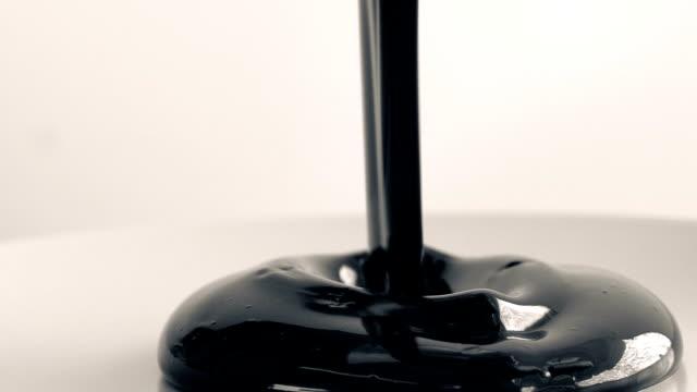 vídeos y material grabado en eventos de stock de pintura negra gruesa se vierte sobre la superficie blanca - pegajoso