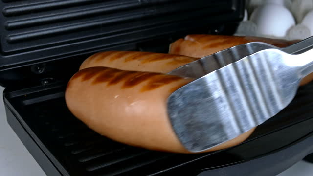 Thick, greasy sausages are fried on an electric grill.