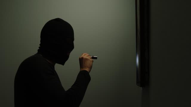 vídeos de stock e filmes b-roll de thief climbs into the house, shines a flashlight on the picture and then escapes - roubar crime